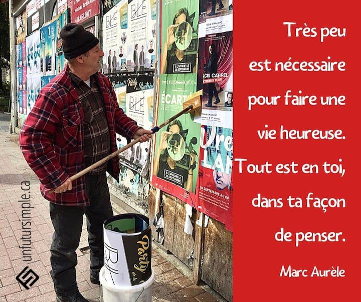Citation de Marc Aurèle: Très peu est nécessaire pour faire une vie heureuse. Tout est en toi, dans ta façon de penser. Homme portant une chemise carottée qui colle des affiches sur un mur avec un balai et un seau.