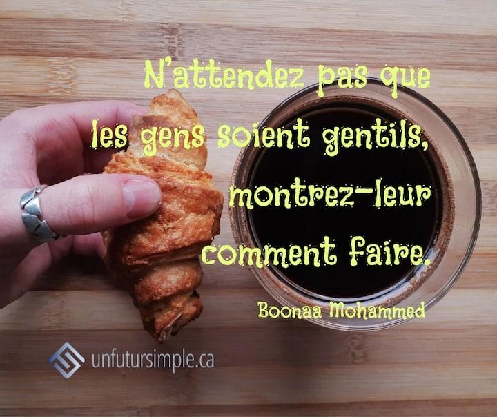 Citation sur la gentillesse de Boonaa Mohammed: N'attendez pas que les gens soient gentils, montrez-leur comment faire. Main avec bague qui tient un petit croissant près d'une tasse de café.