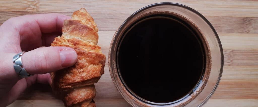 Main avec bague qui tient un petit croissant près d'une tasse de café
